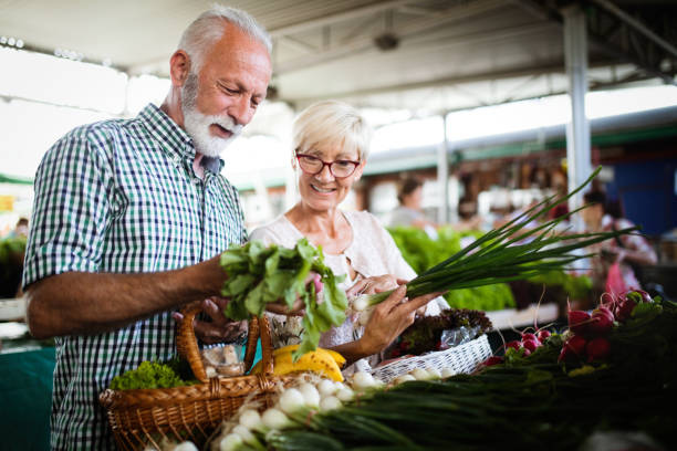 Mature couple shopping vegetables and fruits on the market. Healthy diet. stock photo