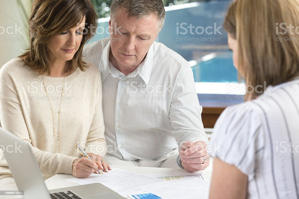 Mature couple signing contract with an advisor stock photo