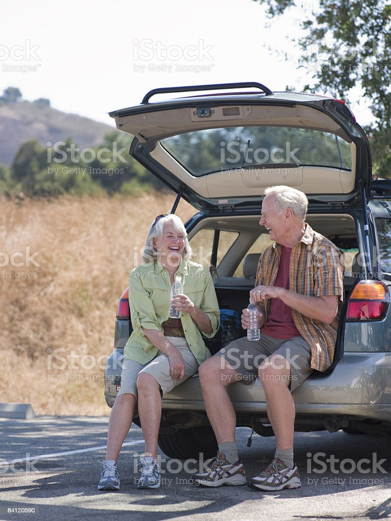 Mature couple sit on tailgate of car. royalty-free stock photo