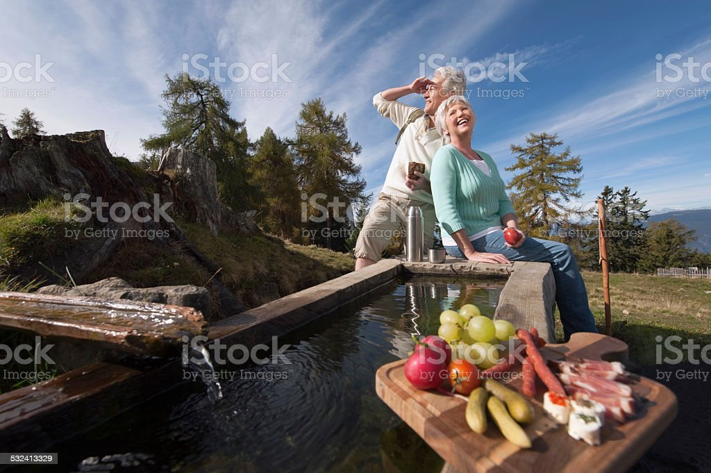 Mature couple sitting at trough having snacks stock photo