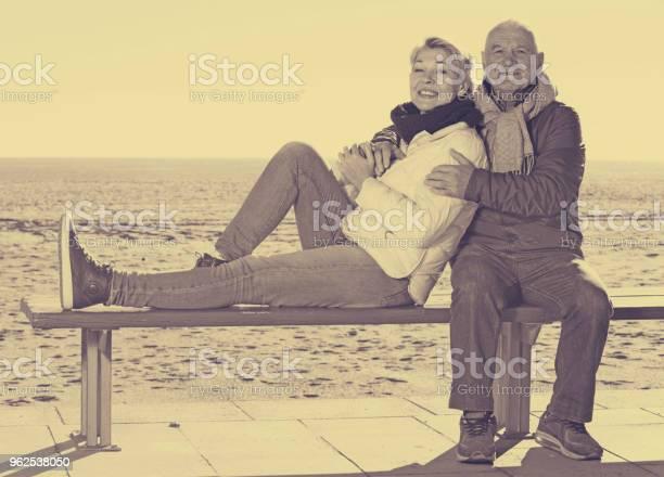 Foto de Casal Maturo Sentado Pelo Mar e mais fotos de stock de Abraçar