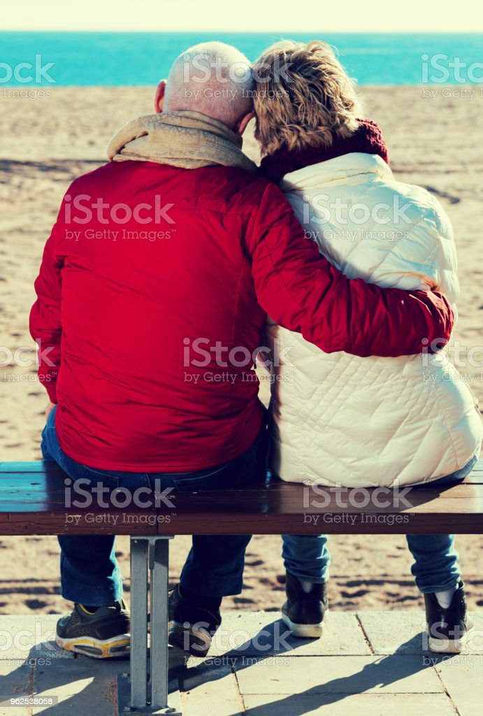 Mature couple sitting by sea - Royalty-free Activity Stock Photo