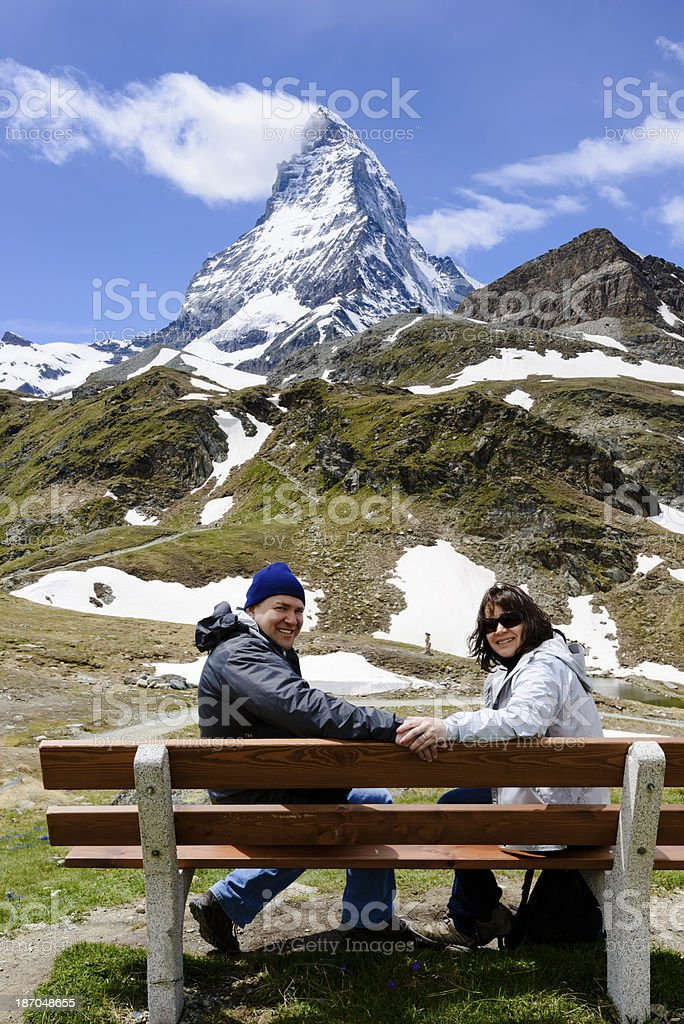 Mature couple sitting on bench in front of the Matterhorn.-XXXL royalty-free stock photo