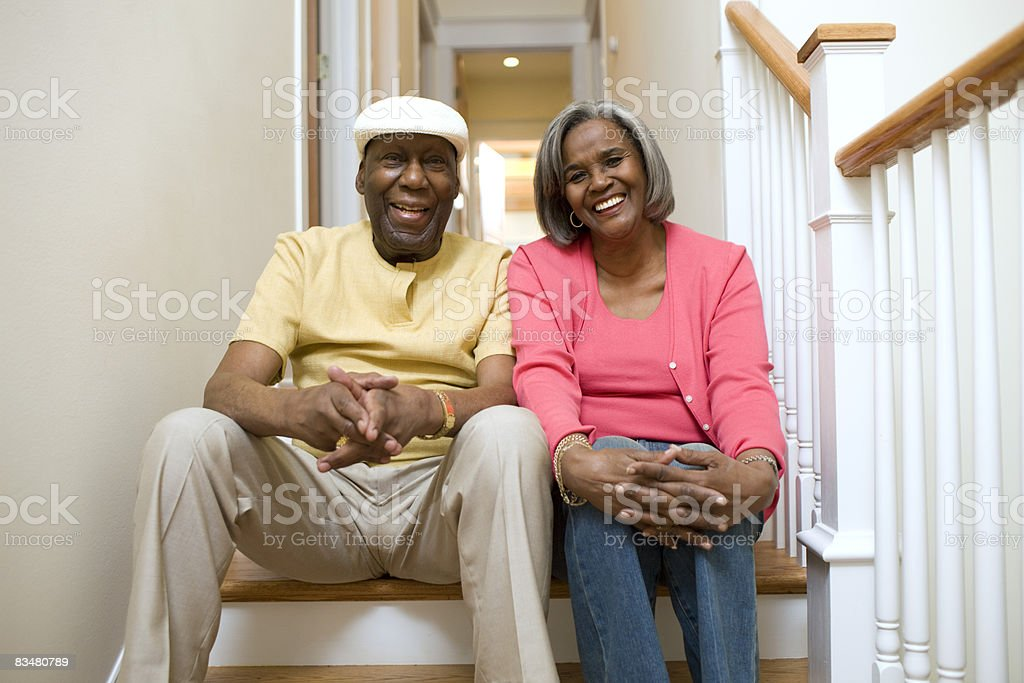 Mature couple sitting on hall stairs at home royaltyfri bildbanksbilder