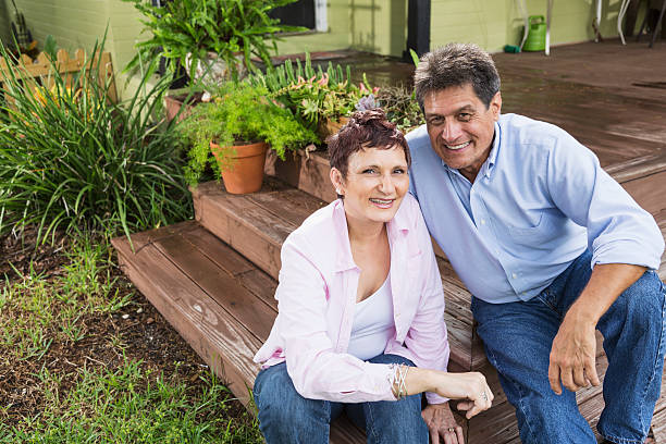 Mature couple sitting on porch steps stock photo