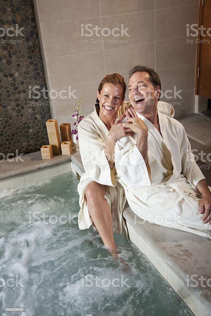 Mature couple sitting on side of hot tub royalty-free stock photo