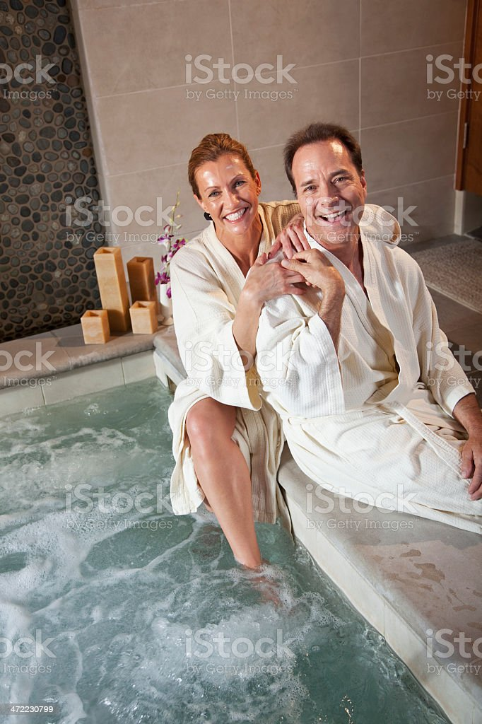 Mature couple sitting on side of hot tub stock photo