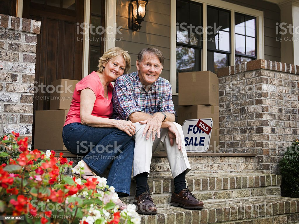 Mature Couple Sitting Outside House With For Sale Sign stock photo