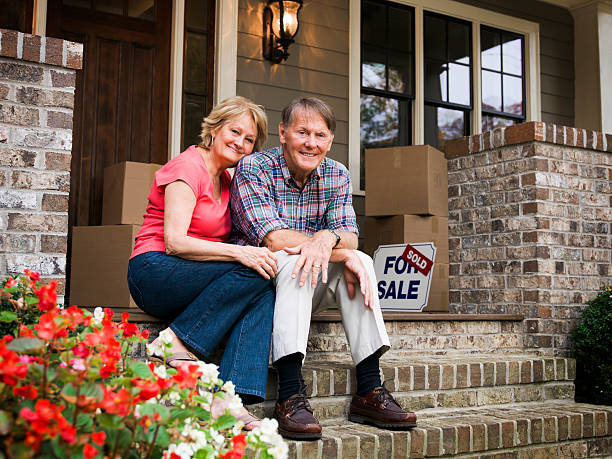 mature couple sitting outside house with for sale sign - senior housing stock photos and pictures
