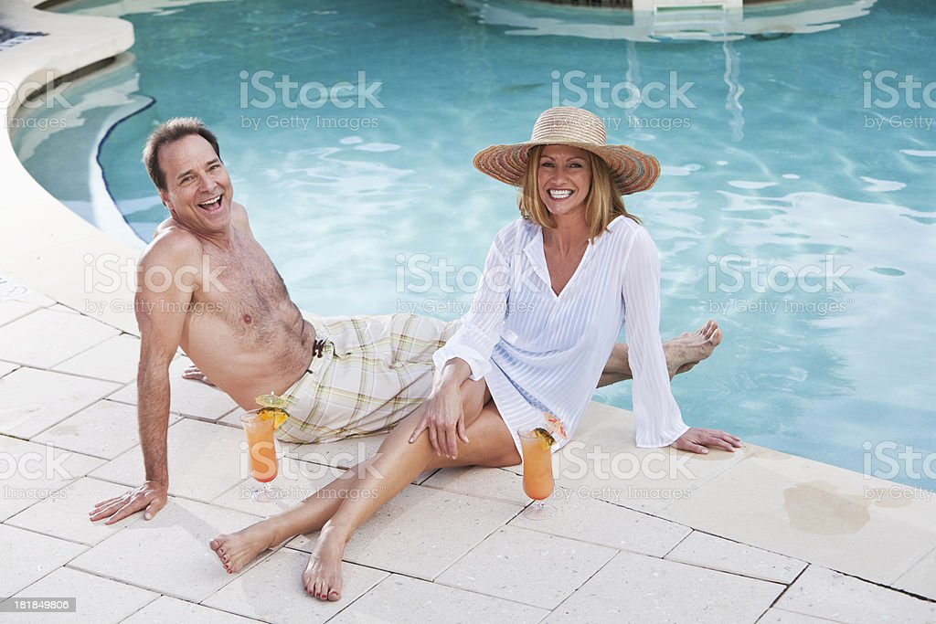 Mature couple sitting poolside stock photo