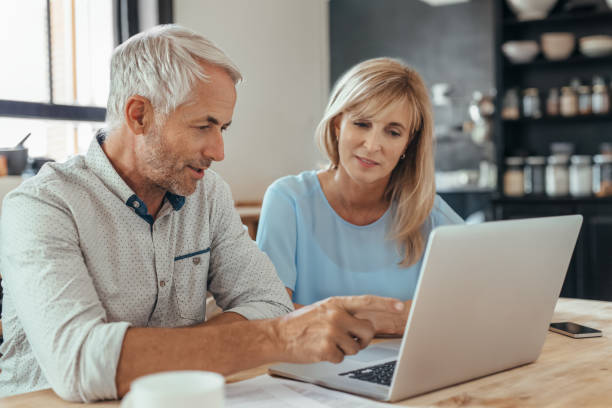 Mature couple sitting together at home doing online banking stock photo