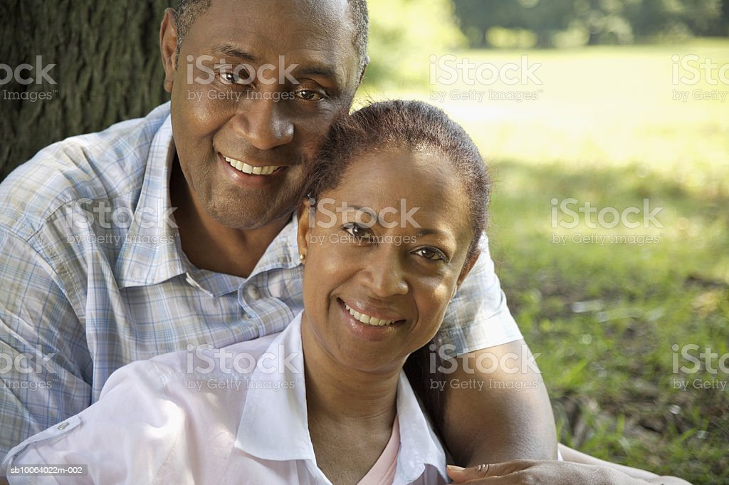 Mature couple sitting under tree in park, smiling, portrait Lizenzfreies stock-foto