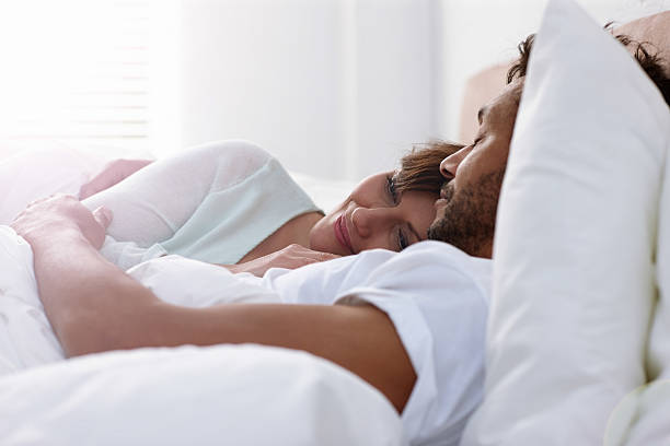 Mature couple sleeping in bed together stock photo