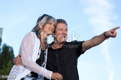 119998253 istock photo Mature couple smiling and pointing 511097119