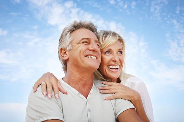 Mature couple smiling Close-up portrait of a mature couple smiling and embracing. young at heart stock pictures, royalty-free photos & images
