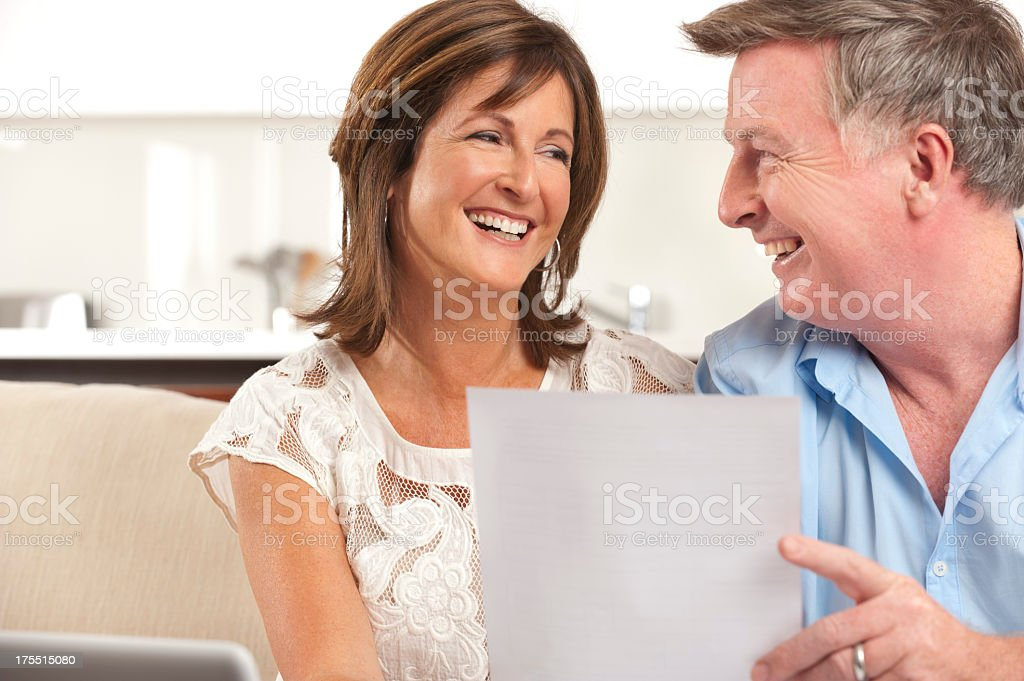 Mature couple smiling reading a document royalty-free stock photo