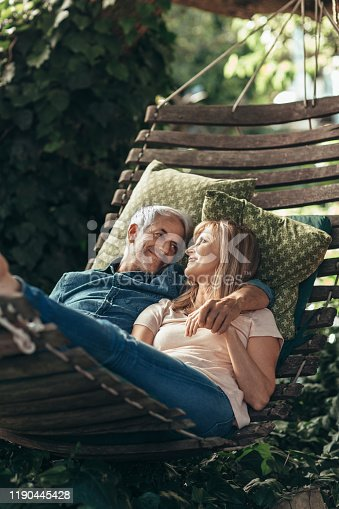 Mature couple smiling contently while relaxing together in a hammock outside under some trees in their backyard