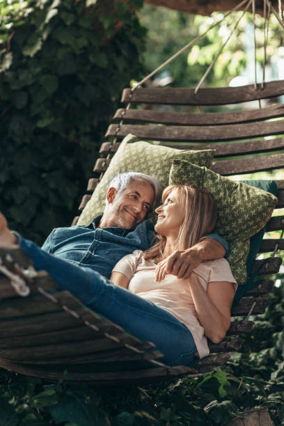 Mature couple smiling while lying together in a hammock outside stock photo