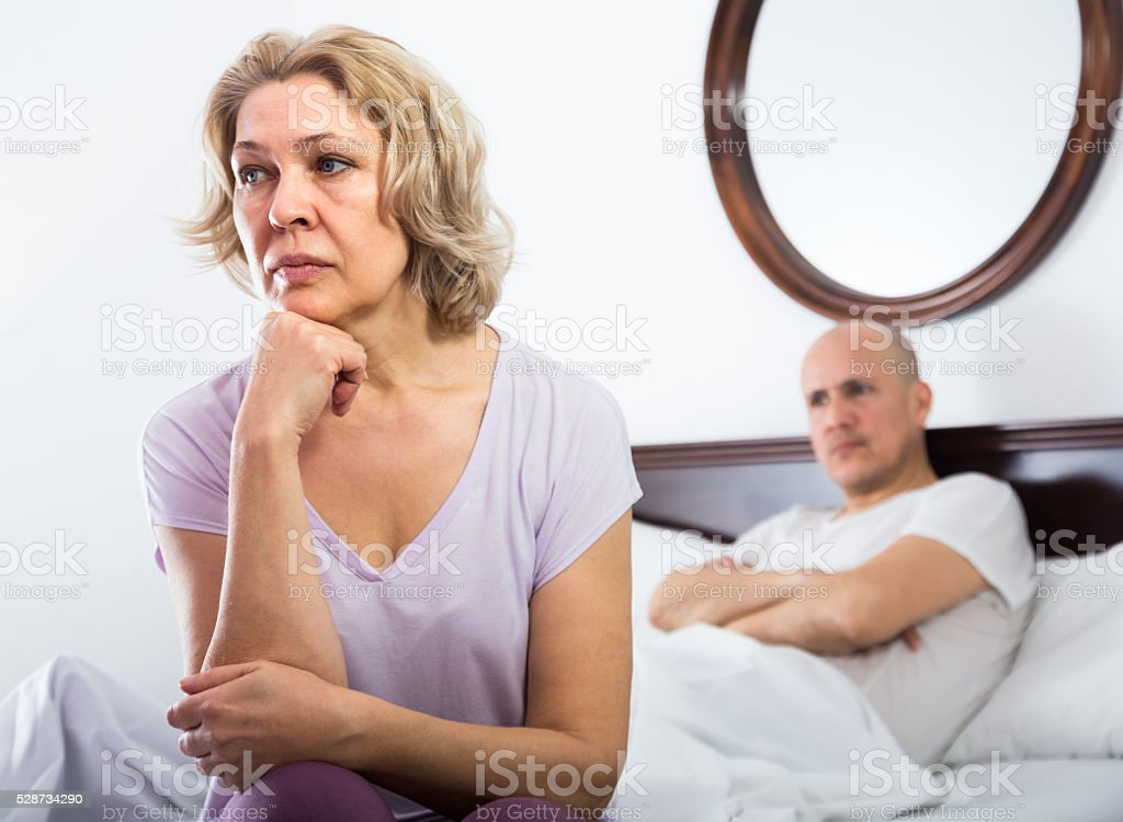 Mature couple sorting out relationships in bed stock photo