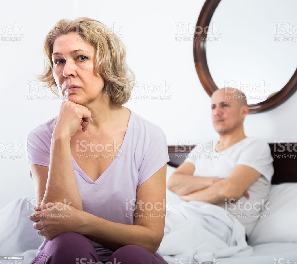 mature couple sorting out relationships in bed stock photo & more