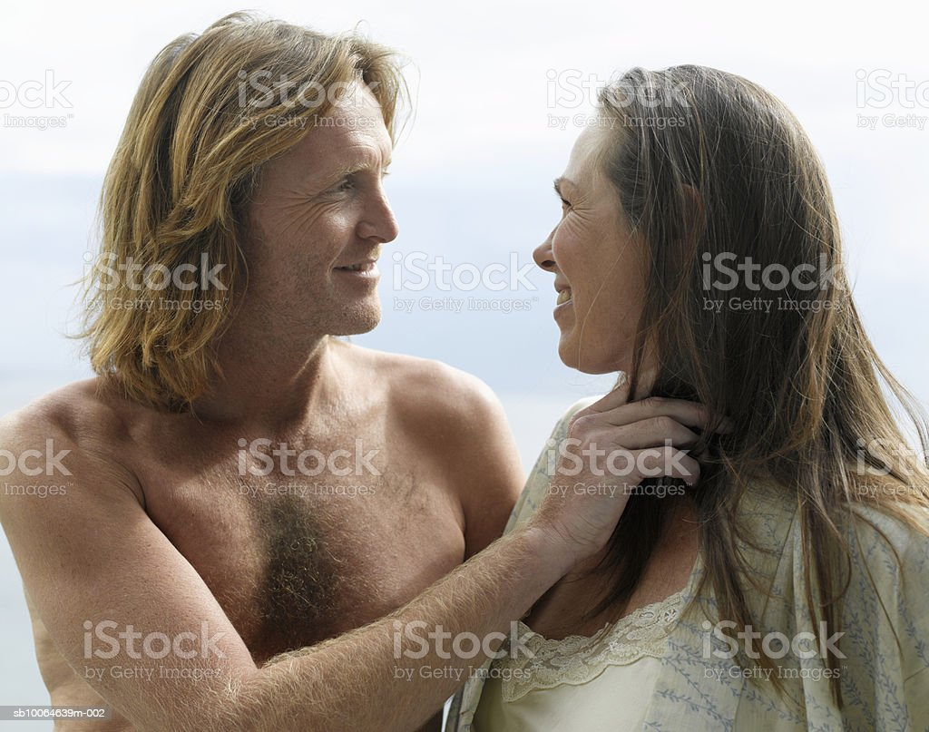 Mature couple standing face to face, smiling royalty free stockfoto