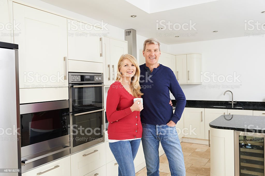 Mature Couple Standing In Beautiful Fitted Kitchen Together stock photo