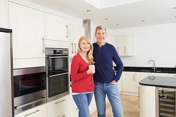 mature couple standing in beautiful fitted kitchen together - 2015 stok fotoğraflar ve resimler