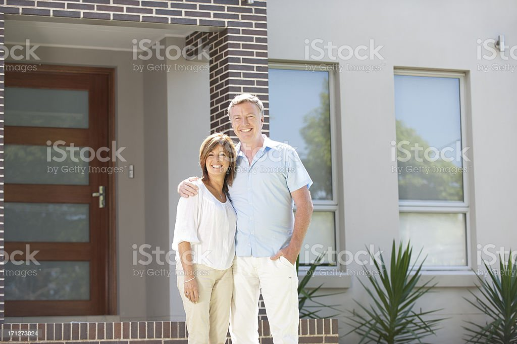 Mature couple standing in front of a modern house royalty-free stock photo