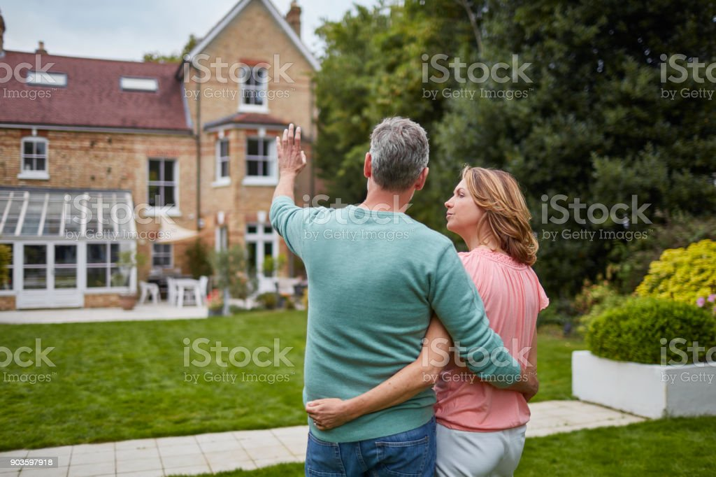 Mature couple standing in front of house stock photo