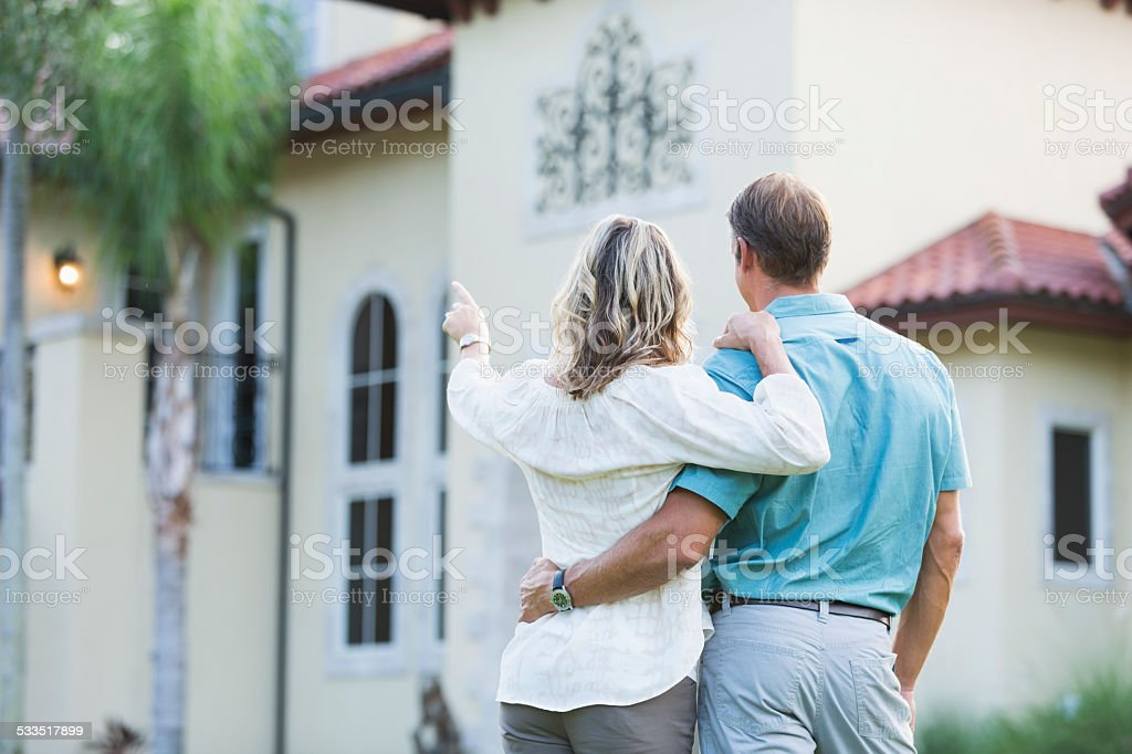 Mature couple standing in front of their mansion stock photo