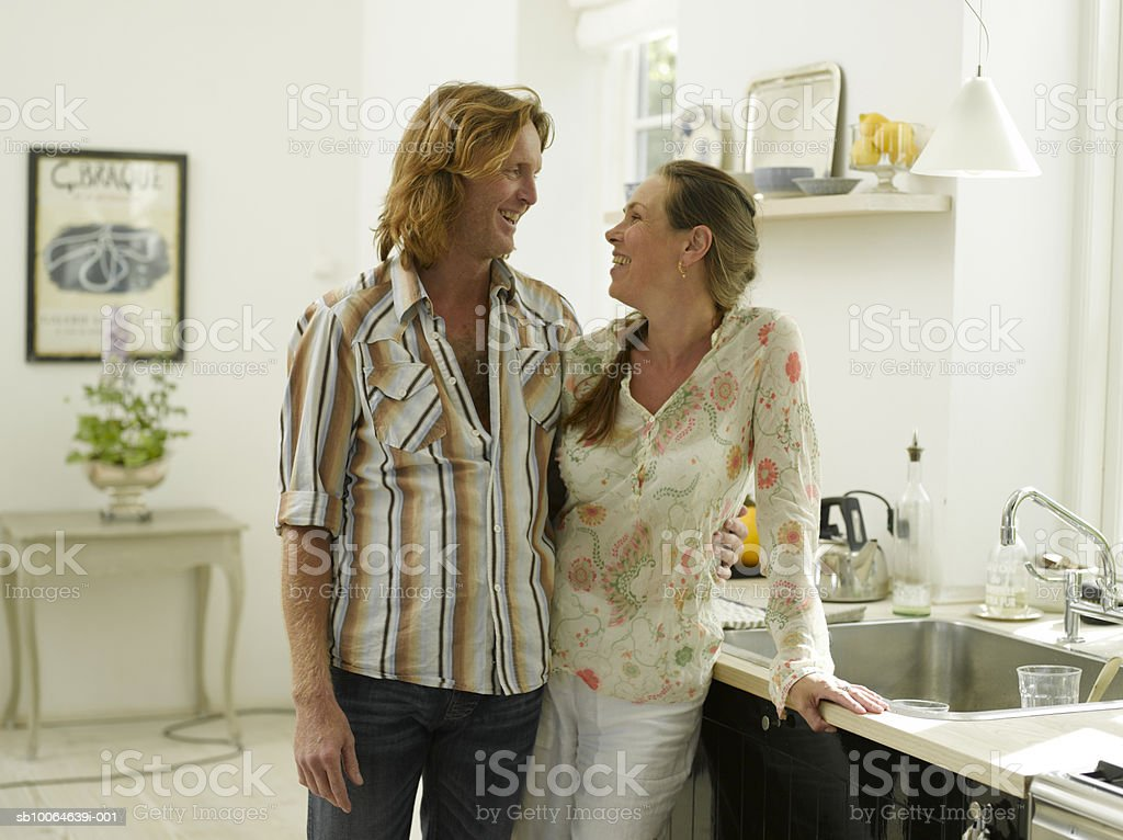 Mature couple standing in kitchen, smiling royalty-free stock photo