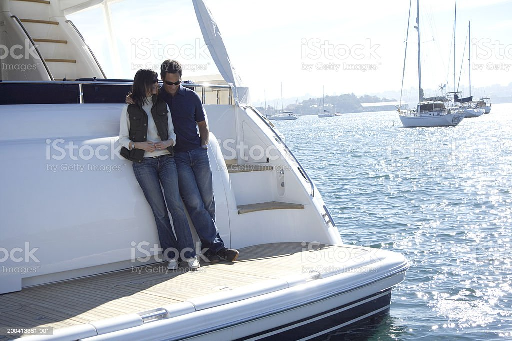 Mature couple standing on stern of yacht in harbour Sydney Harbour, Sydney, Australia. 40-44 Years Stock Photo