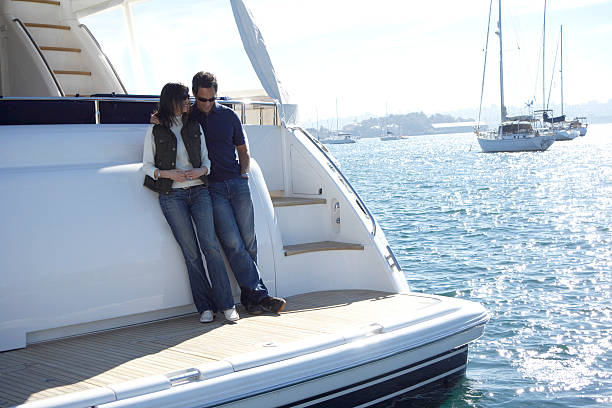 Mature couple standing on stern of yacht in harbour stock photo