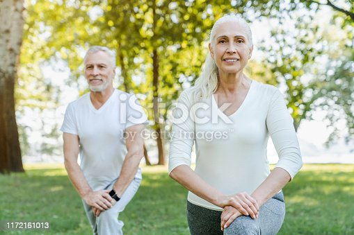 942580016istockphoto Mature couple stretching together in park outdoors before yoga and fitness exercises 1172161013