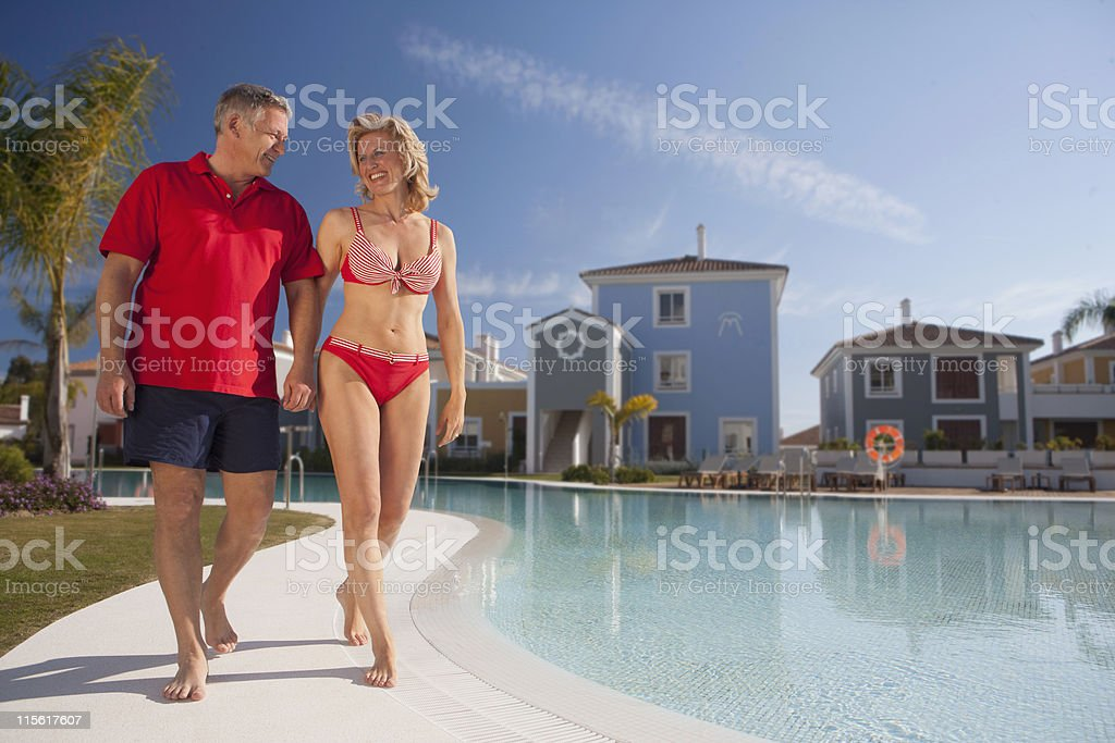 Mature couple strolling by pool stock photo