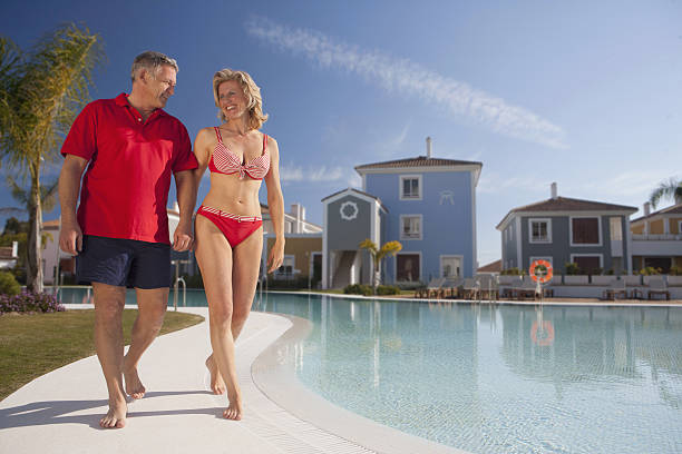 mature couple strolling by pool - older women bikini stock pictures, royalty-free photos & images