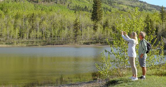 Mature couple take photos of alpine lake on cellphone