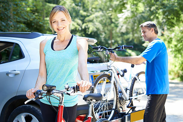 mature couple taking mountain bikes from rack on car - fahrradhalter stock-fotos und bilder
