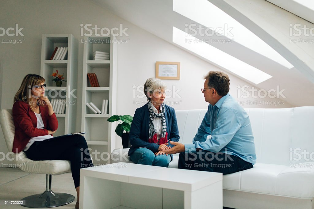 Mature Couple Talking to Counselor stock photo