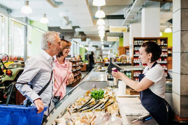 Reifes Paar im Gespräch mit Supermarkt Clerk an Olive Counter – Foto