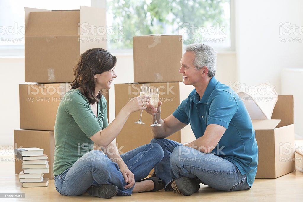 Mature Couple Toasting Champagne Flutes In New House stock photo