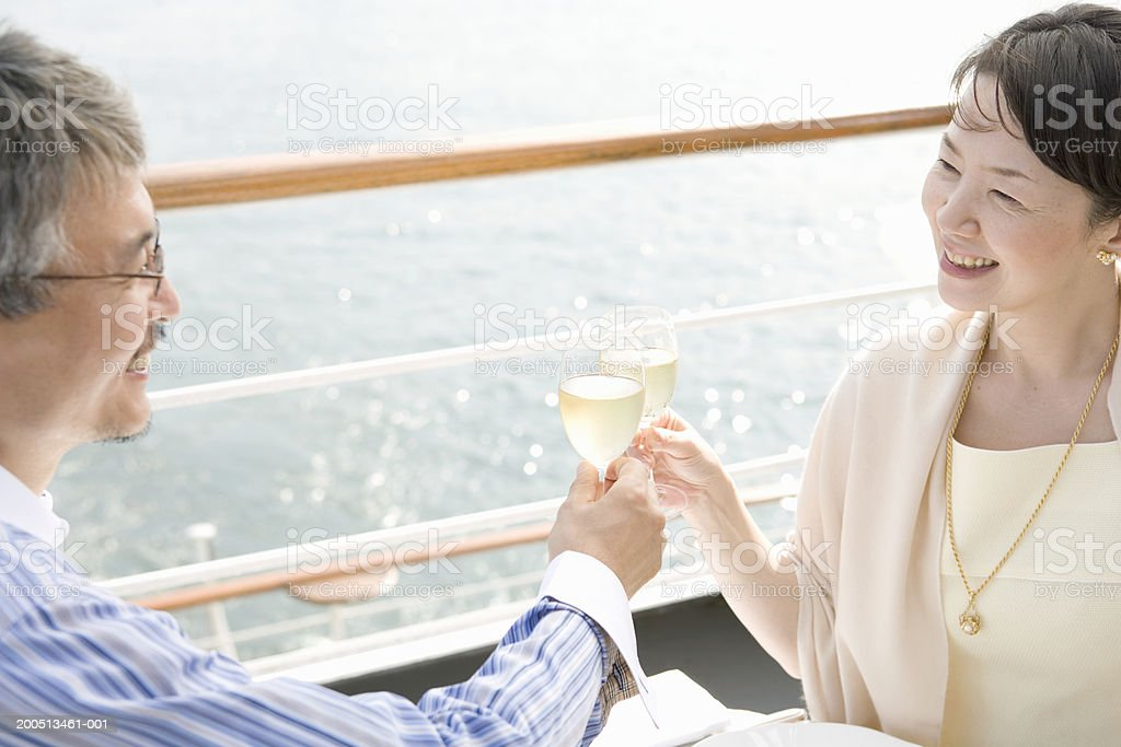Mature couple toasting on deck of cruise ship, smiling royalty-free stock photo
