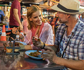 Mature couple trying Thai street food while on vacation in Bangkok, Thailand