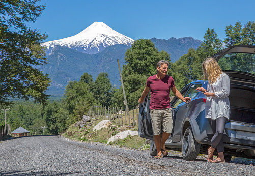 Mature couple use digital tablet outside car on the road to the Osorno volcano