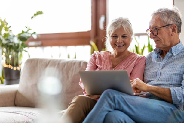 Mature couple using a laptop while relaxing at home Mature couple using a laptop while relaxing at home retirement stock pictures, royalty-free photos & images