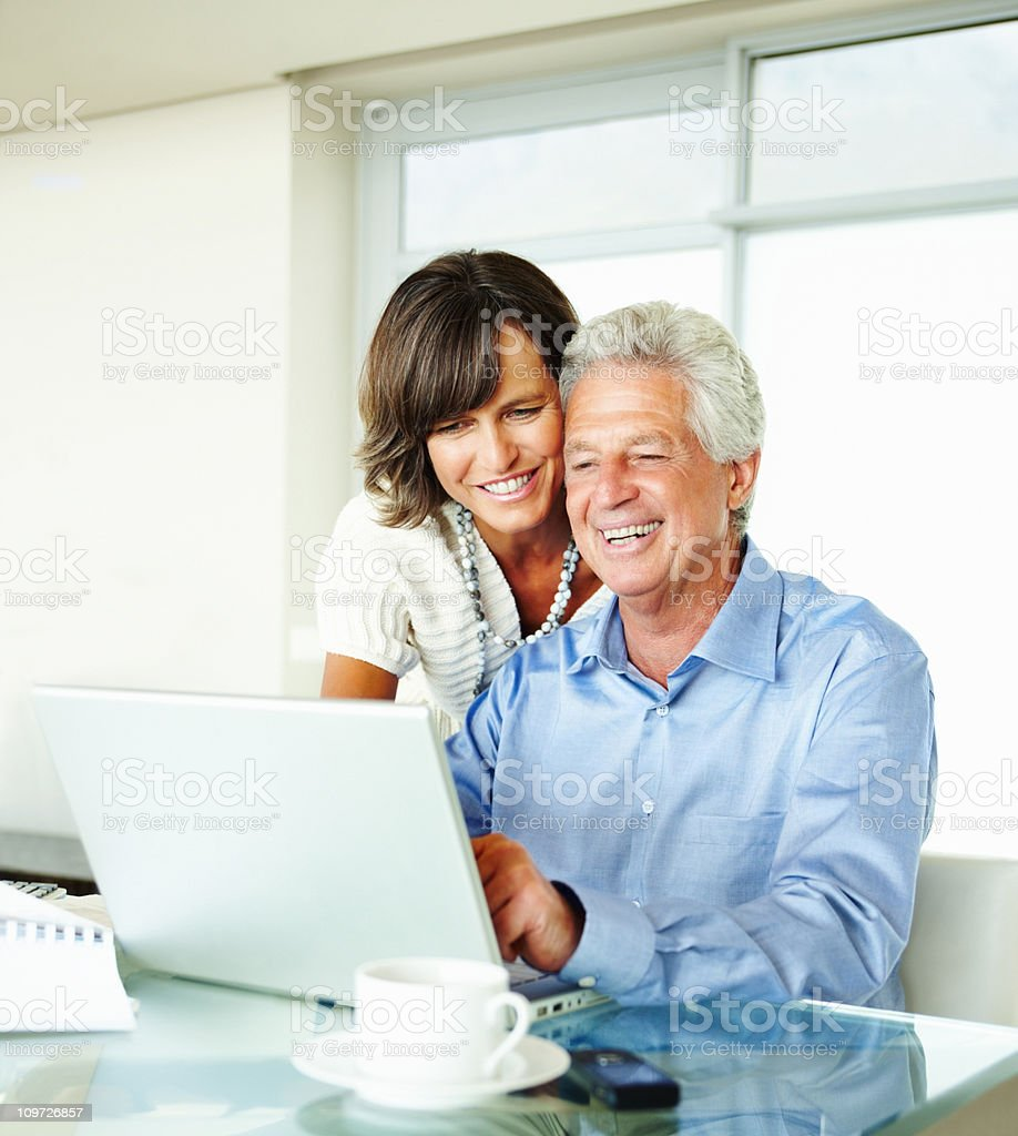 Mature couple using laptop at home and smiling stock photo