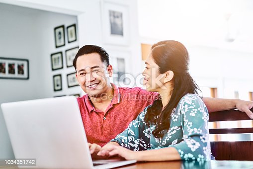 Happy mature man and woman using laptop at table. Couple is discussing over technology in living room. They are in casuals at home.