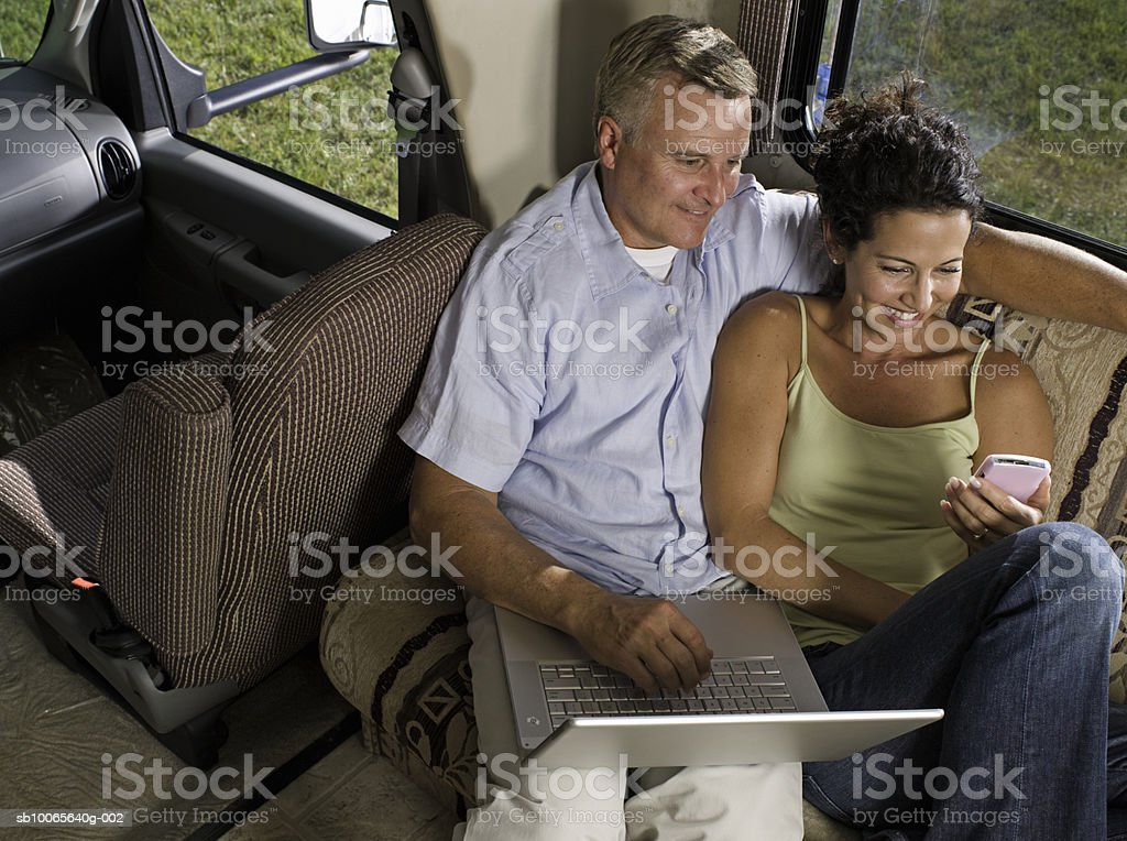 Mature couple using laptop in motorhome, smiling, elevated view royalty-free stock photo