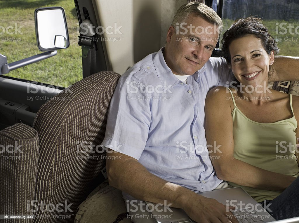 Mature couple using laptop in motorhome, smiling, portrait royalty-free stock photo