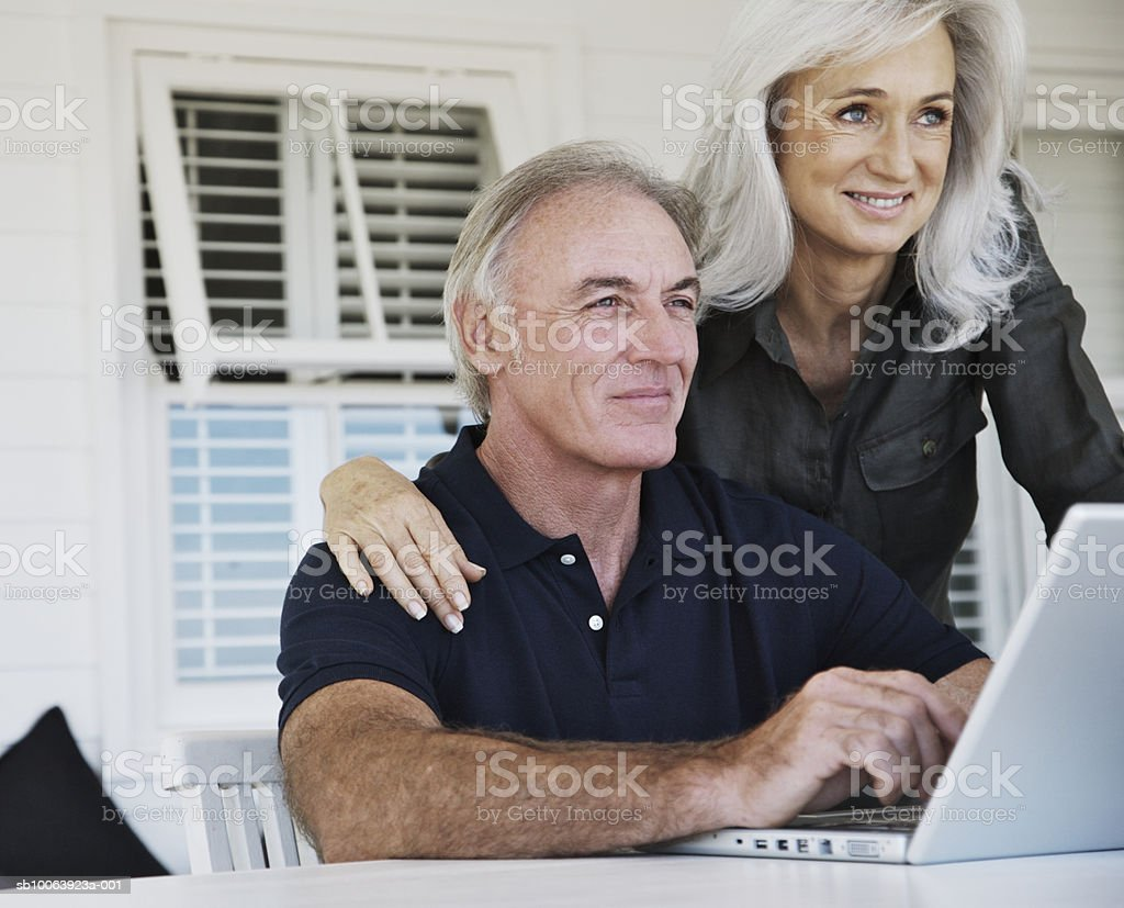 Mature couple using laptop, smiling 免版稅 stock photo